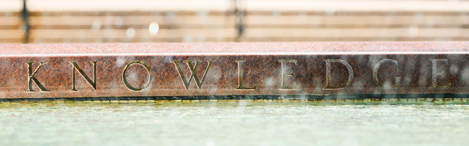 "On Oct. 18, 2017, out-of-focus water spray frames the engraved word 'knowledge"" along the inner edge of the Hagenah Fountain on Library Mall at the University of Wisconsin-Madison."