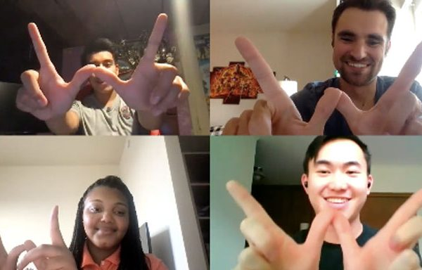 A screenshot of a Zoom video call with four participants holding their hands in the shape of a W.